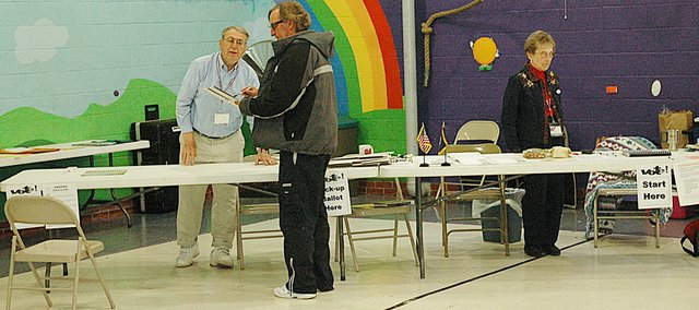 Longtime poll worker Ken Martin, left, answers a question from a voter Tuesday at the Baldwin Elementary School Primary Center polling place. Baldwin City voters chose Ken Wagner as mayor and Bonnie Plumberg and Tom Farmer as city council members. The vote is unofficial until the Douglas County Commission canvasses the vote. Farmer only edged Chris Nichols by seven votes for the second position on the council.