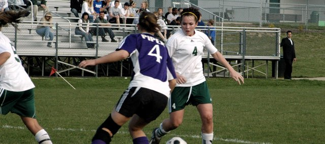 Danielle Price maneuvers around a Piper defender Thursday at De Soto. Price scored one goal in the match, and the Wildcats won, 2-0.