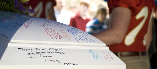 Friends and family of Tonganoxie High School junior Jeremy Elliott paid their last respects during his funeral service and burial Tuesday. His friends were allowed to write messages on his casket saying their goodbyes during Monday's visitation.