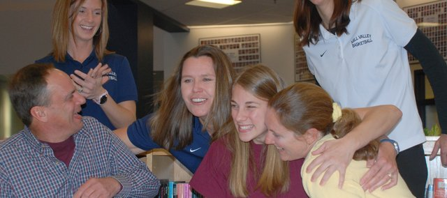 Diana Krull, Mill Valley girls basketball coach, leans in to embrace the Newhouse family after MVHS senior Becky Newhouse signed her letter of intent to play at Johnson County Community College. Pictured at the signing ceremony on April 8 are, from left (seated): Ken Newhouse, Becky Newhouse and Teresa Newhouse, and, standing: Mill Valley assistant coach Kerri Ptacek, Krull and MVHS assistant coach Sherry Meyer.