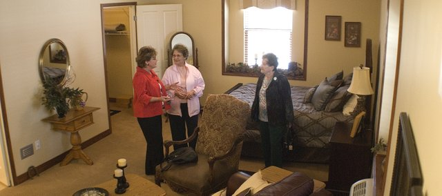 Rosanna Smith, regional director for sales and marketing for Skilled Healthcare, left, takes Elizabeth Banzhaf and Anna Landauer on a tour of a model room at the new Vintage Park Assisted Living Center.