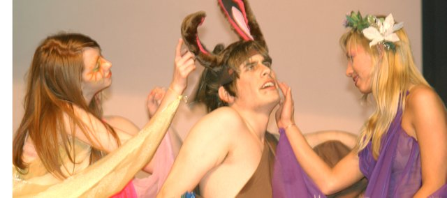 Hannah Smith (left), as the fairly queen Titania with the help of fairies strokes the ears, face and ego of Nick Bottom (Clinton Kyle), transformed into an ass by fairy king Oberon to be the object of his wife's affections while under the spell of a magician flower.