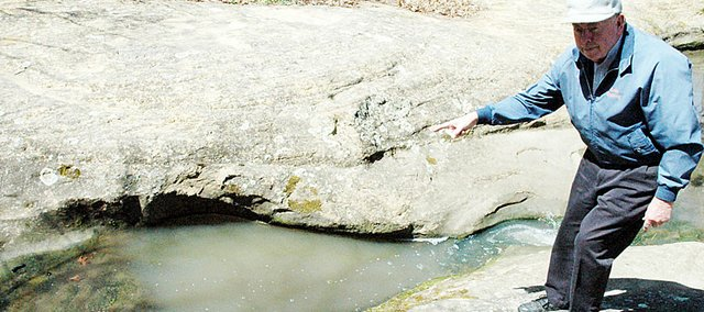 """Marvin Jardon points to the area along Tauy Creek that has formed the """"Hole in the Rock"""" over thousands of years. The area is southwest of the Baldwin Junction and it's hoped that construction on the new U.S. Highway 59 won't impact the historic spot."""