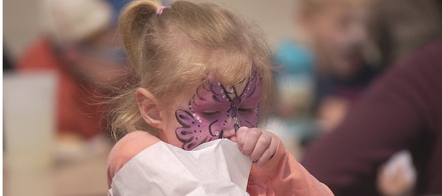 Her face painted as a butterfly, Mary Kueter digs into a bag of goodies at last year's Spring Fling. The successful FCB Bank community event will return Saturday to downtown.