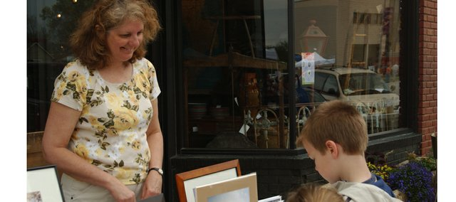 Local artist Rose Burgweger displays photographs, prints, calendars and other works that feature rural De Soto at the Spring Fling Saturday in downtown De Soto.