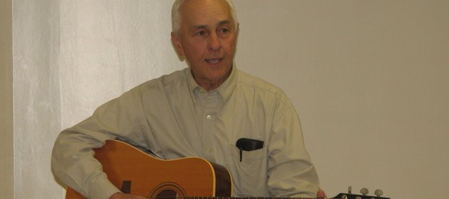 Folklorist and English professor Jim Hoy plays guitar and sings a tune about life on the trail. Hoy came to the Basehor Community Library Tuesday night to share stories about the original cowboys.