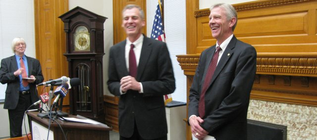 Gov. Mark Parkinson, left, and Earl Watkins, president and chief executive officer of Sunflower Electric Power Corp., share a laugh during a news conference Monday announcing a proposed agreement that will allow Sunflower Electric to build a coal-burning power plant in southwest Kansas.