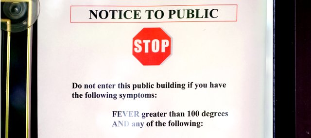 A sign, posted at City Hall, warns ill residents with flu-like symptoms to avoid public buildings.