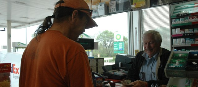 Bill Stephan counts out money to Stephan's Service customer Tim Creasman. Stephan is working for his son Craig, who currently owns the gas station and auto body shop, but was the former owner from 1959 to 2002.