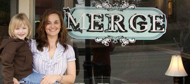 Amy Aaron holds her 5-year-old daughter Chyanne in front of her new store in downtown Tonganoxie.
