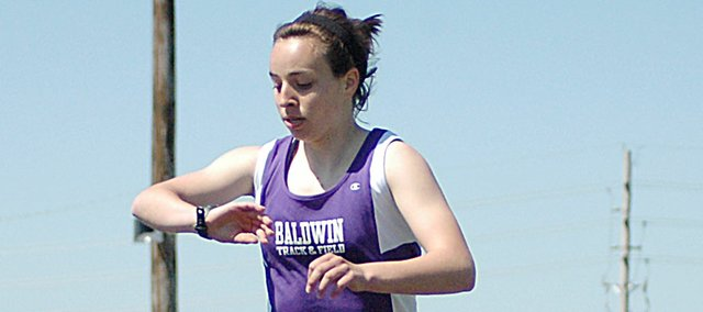 Baldwin Junior High School eighth grader Kaitlyn Barnes stops her watch as she crosses the finish line easily winning the 800-meter run Saturday afternoon at the Frontier League meet in Gardner. Barnes set two meet records and helped set a third on a relay as the BJHS eighth grade girls won the team title.
