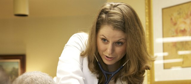 Courtney Huhn, a second-year Kansas University medical student, consults last week with Mary Williams, a resident at Kansas City Presbyterian Manor in Kansas City, Kan. Huhn, of Lansing, didn&#39;t hesitate to sign up for the Kansas Student Medical Loan Program. She said it was a win-win situation for her. The program pays for her tuition and provides $2,000 for monthly expenses. In return, she will become a primary care doctor and work in a rural Kansas community. The program will save Huhn about $170,000 over four years.