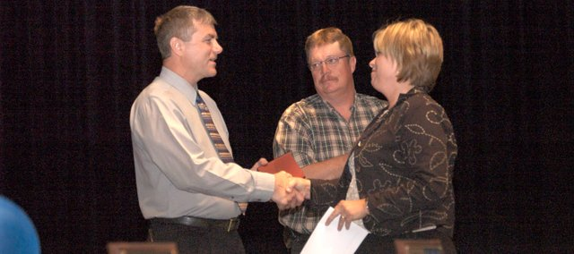 Robin Colgrove, right, shakes hands with Tonganoxie FFA adviser Randy Kraft after FFA members' parents presented Kraft with a clock as recognition for his 31 years of teaching agriculture classes and serving as adviser. Colgrove read from letters submitted from Kraft's past students. The recognition took place during the 28th Annual Tonganoxie FFA Chapter banquet, which was Thursday at THS. Looking on is Mike Kissinger.