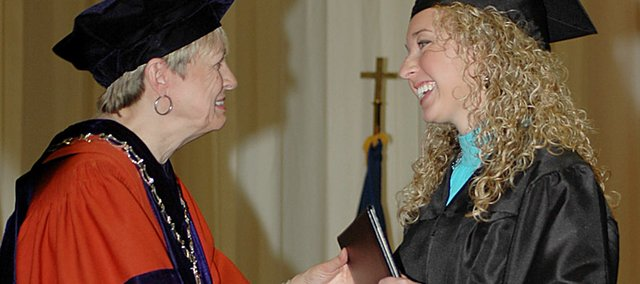Baker University President Pat Long, left, shakes the hand of graduate Annie Parr as she receives her diploma Sunday afternoon. Parr, a 2006 Baldwin High School graduate, earned her degree in three years.