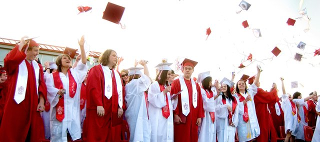 Tonganoxie High School seniors throw their caps in the air after officially becoming THS graduates Saturday evening at Beatty Field in Tonganoxie.