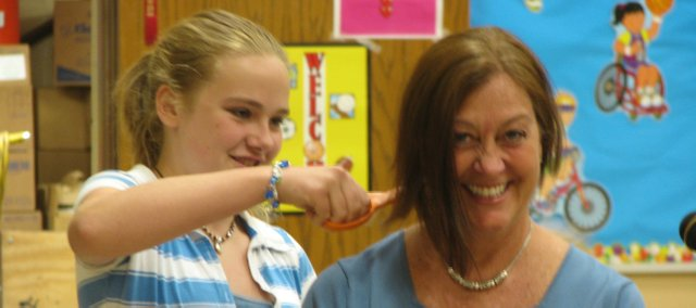 Basehor Elementary sixth-grader Jade Provence snips away at principal Teri Boyd's hair. Boyd told the elementary students they could cut her hair at the end of the year if they met their reading goals. The hair was donated to Locks of Love.