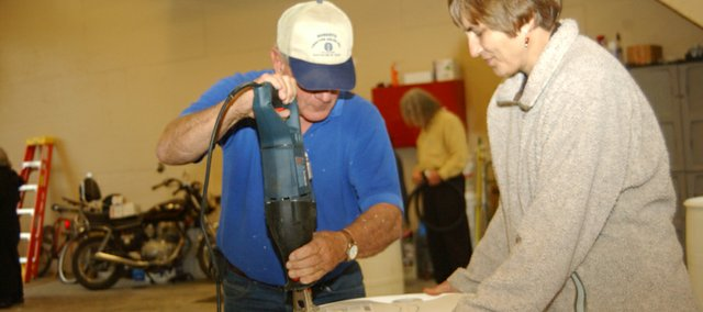 Tom Bach of the Hillsdale Water Quality Project cuts an access hole in the top of Lori Murdock's new rain barrel at a May 12 workshop at the De Soto waste water plant to encourage the use of a item that went out of favor in the past half century