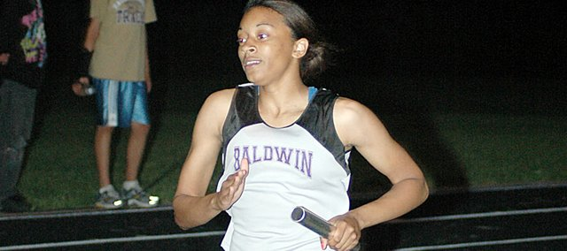 Baldwin High School junior JaBryanna Wellington anchors the girls' 1,600-meter relay Friday night. The Bulldogs won the event to wrap up their team championship.