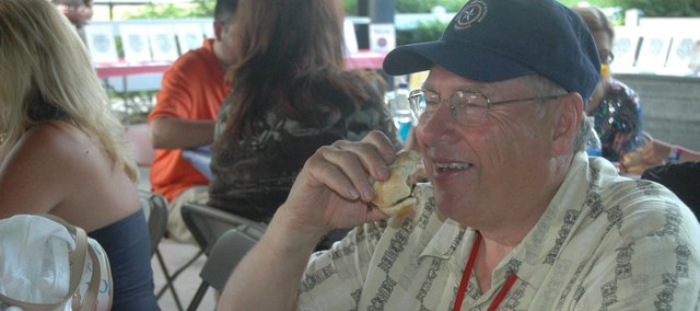 Dale Abernathy, of Fountain, Colo., enjoys some food catered by Oklahoma Joe's Barbecue during Friday night's BBQ Blues Party at the Great American Barbecue Festival at Capitol Federal Park at Sandstone. The BBQ Blues Party was a featured event during the festival of music and barbecue contests.