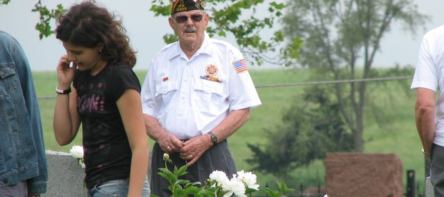 Basehor VFW Trustee Wilbur Grisham (center) looks out at the decorated gravesites at Glenwood Cemetery Monday, and Hayley Luna (left) studies the headstone before her. The VFW played host to a Memorial Day service at the cemetery to honor deceased United States veterans.