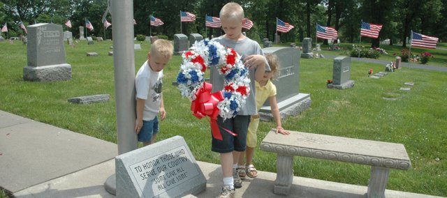 Three Edwardsville children place a Memorial Wreath at the base of the flagpole Sunday during the Memorial Day services at Edwardsville Cemetery.