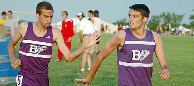 Baldwin High School freshman Brian Wright, left, high-fives his brother, senior Connor Wright, after the siblings qualified for the state meet in the 800-meter run Friday evening.