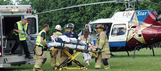 Emergency personnel loaded William L. Harris, 17, Wellsville, into a helicopter ambulance after he was struck by a car while attempting to run across U.S. Highway 56 at 4:55 p.m. Thursday. Harris was taken to the University of Kansas Medical Center where he's in good condition, according to Baldwin City Police Chief Mike McKenna.