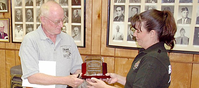 John Brandt, left, director of the Douglas County Crime Stoppers, presents Baldwin City Police Cpl. Kim Springer with the 2009 Distinguished Service Award for her work as the School Resource Officer at Monday's city council meeting.