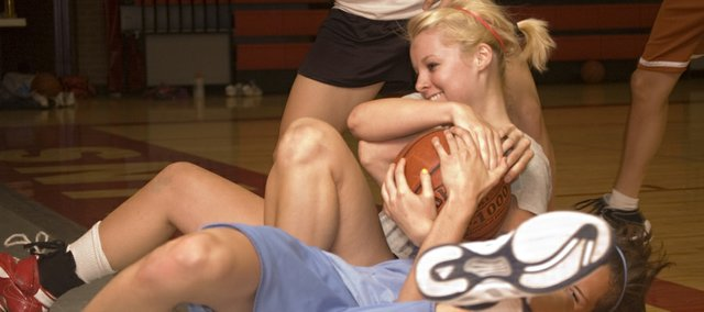 Brittani Papa fights for a loose ball with Jennifer Whitledge on Thursday at Tonganoxie High girls basketball camp.
