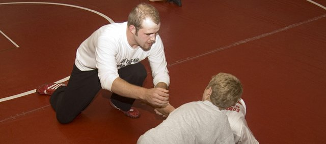 Wyatt Coffin, a 2008 Tonganoxie High grad, instructs two young wrestlers at Tongie Kids Wrestling Camp of Champs on Wednesday, June 10 at THS.
