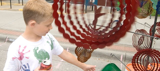 Garrett Vaughn, 8, plays with some wind spinners from the Enchanted Oasis booth.