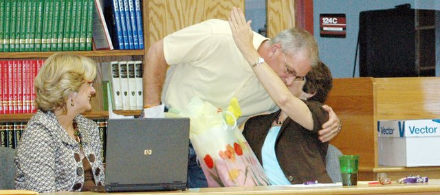 USD 491 Board of Education President Kenny Massey hugs outgoing board member Brenda Clark during Thursdays board meeting as Belinda Rehmer looks on. Clark, Bob Rice and Jim Martin were recognized for their time on the board.