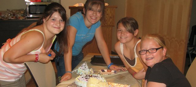 Teens in the Basehor Community Library summer reading program participated in a cake-decorating contest Tuesday to express themselves through food. (From left)  Katey Trower, Brittni Guthrie, Chase Ryder and Julia Stevens pose by their winning cake.
