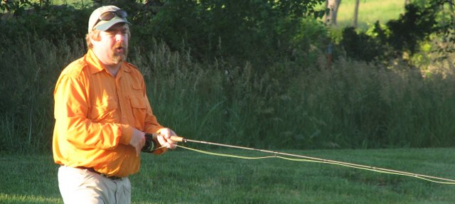 Cabela's fly fishing instructor Tim Giger demonstrates Monday how to cast a line on the lawn of the Basehor Community Library.