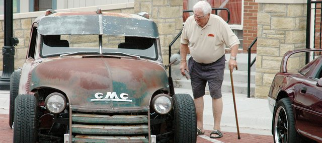 Longtime Baldwin City resident Merle Venable takes a look at one of the antique cars on display during Saturday's Planes, Trains and Automobiles event. There were cars, motorcycles and bikes on display downtown, train rides at the Midland Railway and plane rides at the Vinland Airport.