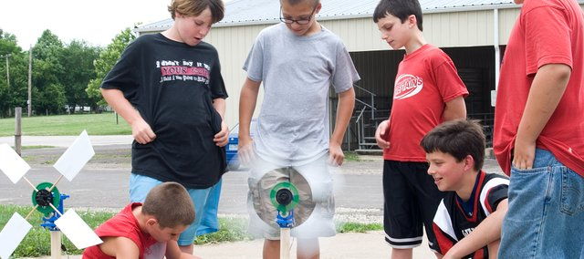 4-H tech campers gather around a wind turbine they made during the camp.