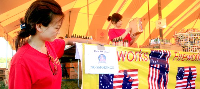 Ally Li, left, and Nancy Gao, right, help set up a fireworks tent Tuesday morning in Lawrence. The two women are employed at a warehouse in China that is owned by Eudora-based Garrett's Fireworks and are visiting the United States to see the other side of the business.