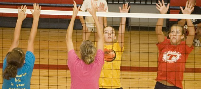 Rachel Sparks and Abby Eisman practice their block approaches during a drill at Tonganoxie High volleyball camp.