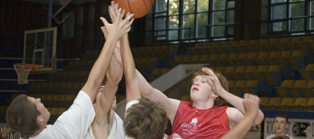 Dane Erickson, Tonganoxie High center, reaches for a rebound during a summer league game at Rockhurst University in Kansas City, Mo.