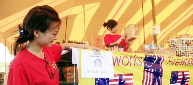 Ally Li, left, and Nancy Gao, right, help set up a fireworks tent in Lawrence Tuesday morning. The two women are employed at a warehouse in China that is owned by Eudora-based Garrett&#39;s Fireworks and are visiting the United States to see the other side of the business.