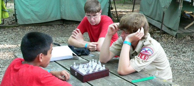 A group of Boy Scouts uses down time to play a game of chess during summer camp at the Theodore Naish Scout Reservation. Pictured (clockwise from left) are Jacob Penrod, Jimmy Klingele and Matthew Taber.