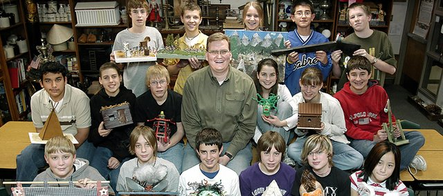 Award-winning teacher Keil Hileman and a number of his former students show off some of the items he collected in his classroom. Hileman is working to expand his popular museum connections class to other schools in De Soto USD 232, including Monticello Trails Middle School and De Soto High School.