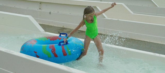 A young waterslide rider pulls her own tube after completing a ride down the Bahnzai Pipeline, a 42-foot tall twisted water ride.