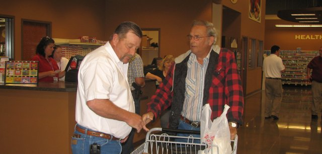 Benchmark Management owner Ed McIntosh (left) surveys Bob Moore's groceries Friday morning at the Wolf Creek Marketplace grand opening.