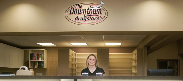 Shelves at The Downtown Drugstore are starting to fill up. Owner Sarah Breuer is pictured Tuesday at the drugstore, which is in the former Holst Pharmacy building in downtown Tonganoxie. Breuer, formerly a pharmacist with Holst Pharmacy, is starting the new business with her husband, Scott.