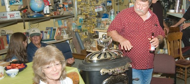 Phyllis and Roger Shilling hang out near their new Great Western wood stove, which friends gave to them at a surprise gathering Thursday at their downtown store, Shilling Electric. The refurbished stove is about a century old.