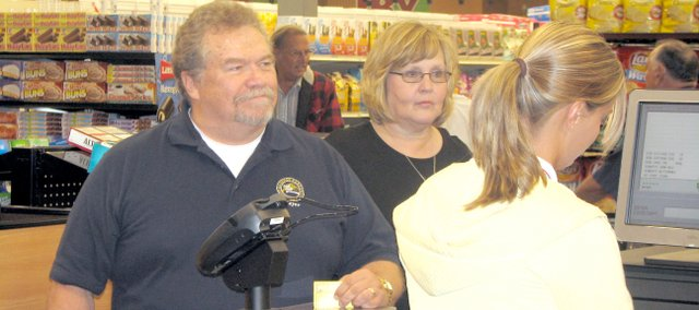Basehor mayor Terry Hill and his wife, Christine, watch as a checker scans their groceries Friday morning at the Wolf Creek Marketplace grand opening. Hill spent the first dollar in the Basehor store that day.