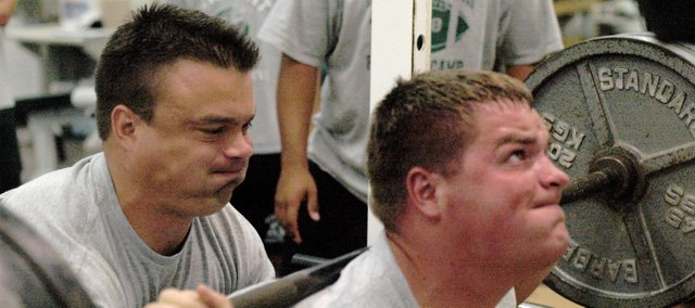 Brian King, left, spots De Soto senior football player Daniel Davis as he squats 455 pounds during the team's weight lifting session Monday morning in De Soto. King is the new strength and conditioning coach at De Soto High School.