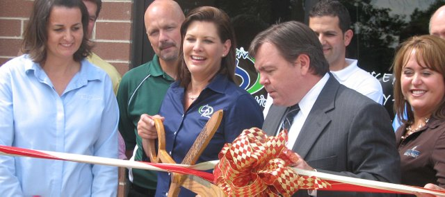 Creative Promotions owner Valarie Grant (center) snips away at the ribbon during a ribbon cutting ceremony July 16 at the business's grand opening. Creative Promotions puts a businesses logo on items such a pens and mugs for promotional reasons.