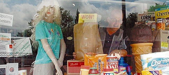 The front window at Kite Video has been filled and refilled with contributions for the Community Food Pantry during the past week plus. Here, Ed Kite, right, adds in some food while mannequin Trixie looks on. The food drive continues through Monday and people can drop off donations until then.